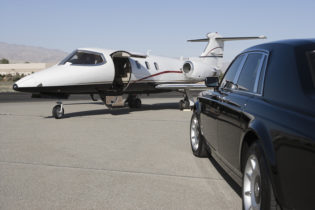 Limousine and private jet on landing strip